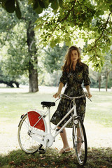 Vintage model in the park with bicycle