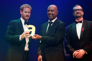 Britain's Prince Harry receives a posthumous Attitude Legacy Award on behalf of his mother Diana, Princess of Wales, from Ian Walker and Julian La Bastide at the Attitude Awards in London
