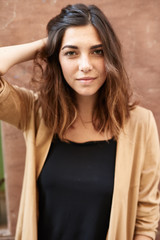 Beautiful girl in beige and black touching her hair.