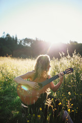 Young woman sitting in field at sunrise playing classical guitar and singing