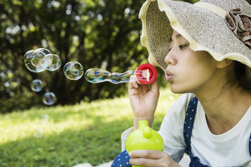Woman sitting on picnic cloth and blowing bubbles on green grass