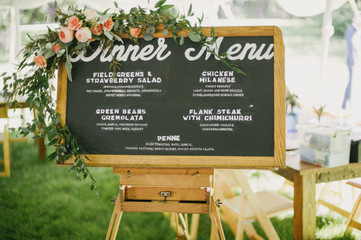Handmade hand painted dinner menu on chalkboard sign with flower garland