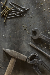 Different hand tools, nails and screws on dark metal background