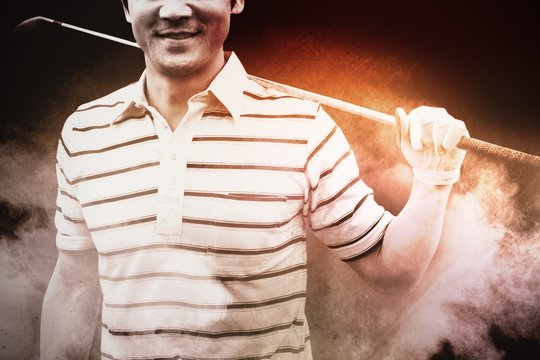 Composite image of golfer standing and holding his club smiling