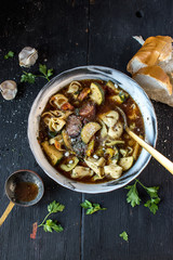bowl of tortellini soup with sausage and zucchini top view