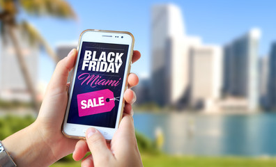 Black Friday Miami. Girl in Miami holding a smartphone with a Black Friday advertising on the screen. Marketing, ecommerce, cell phone publicity.