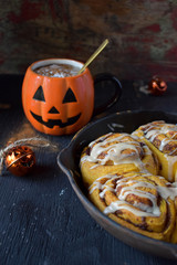 pumpkin cinnamon rolls in cast iron pan with Halloween decorations