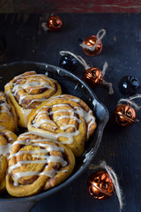 pumpkin cinnamon rolls in cast iron pan with Halloween decorations
