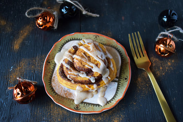 pumpkin cinnamon roll on Halloween plate top view
