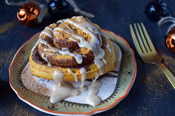 pumpkin cinnamon roll on Halloween plate closeup