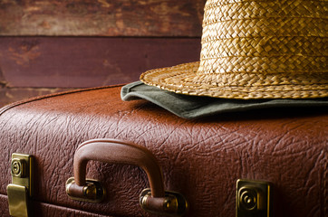 Old vintage, retro suitcase and hats on dark background. Travel concept