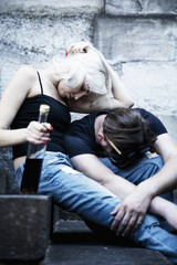 Couple sitting on the table and drinking alcohol. Drunk young people sleeping on the stone stairs. (alcoholism in family, pain, pity, hopelessness, social problem of dependence, depression concept)