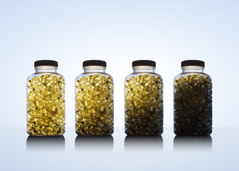 Amber glow through bottles full of fish oil omega 3 and vitamin D supplement gel capsules. on blue background