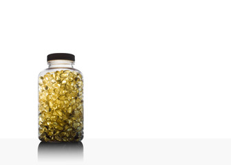 Amber glow through bottle full of fish oil omega 3 and vitamin D supplement gel capsules. on white background