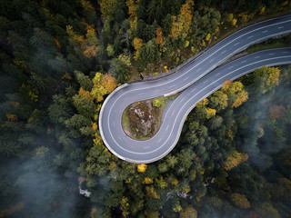 Foto op Plexiglas Luchtfoto street from above trough a misty forest at autumn, aerial view flying through the clouds with fog and trees
