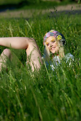 Young blond girl in sparkling hat lies on green grass