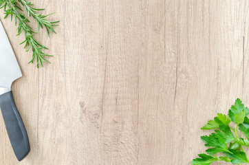 Herbs with knife on wood table