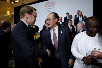 Deutsche Bundesbank President Jens Weidmann (L) shakes hands with World Bank President Jim Yong Kim