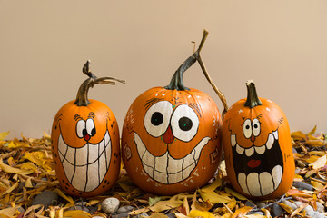 Three smiling and laughing pumpkins with painted faces that have oval eyes and big teeth. The pumpkins are photographed against a beige background..