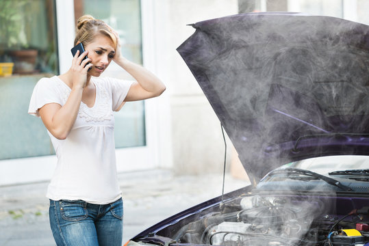 Woman Using Mobile Phone While Looking At Broken Down Car