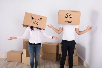 Couple Wearing Cardboard Boxes Shrugging