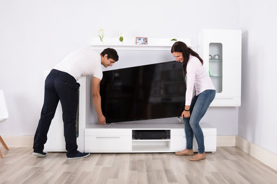 Couple Carrying Flat Television Screen