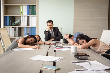tired exhausted young business man and woman sleeping in office