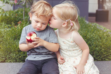 Group portrait of two white Caucasian cute adorable funny children toddlers sitting together sharing apple food. Kids kissing each other. Love friendship childhood concept. Best friends forever