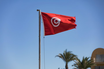 Tunisian flag waving in the blue sky in the beach