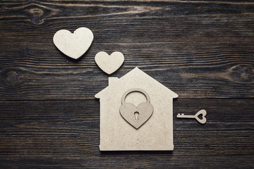 Handmade home symbol with lock-heart and key on wooden background with copy space.