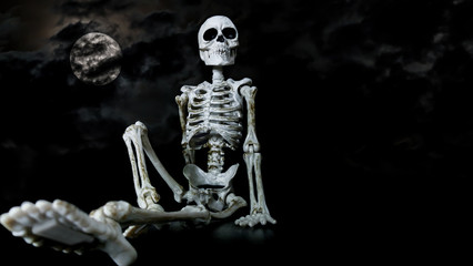 Halloween toy skeleton sitting down in a relaxed manner with the moon and dark clouds behind.