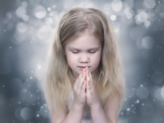 Little girl Praying with eyes closed. Child like an angel