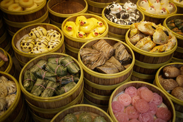 Arrangment of various dim sum in bamboo steamer with chinese snack pastry