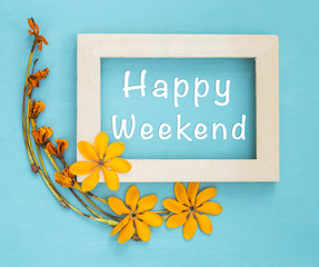 Happy weekend in wooden frame with yellow flower on blue background