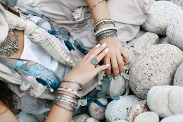 close up of boho styled woman hands with silver jewelry