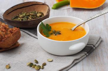 Pumpkin cream soup with pumpkin seeds on textile canvas background