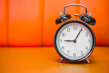 retro style bell clock in the morning on orange background