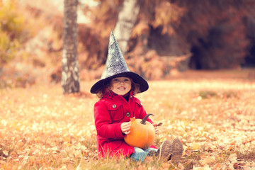 Little girl wearing Halloween witch hat and warm red coat, having fun in autumn day. Wall mural