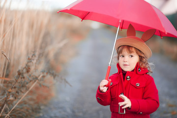 Little girl walking with umbrella, autumn day.