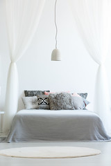 Patterned pillows on canopy bed