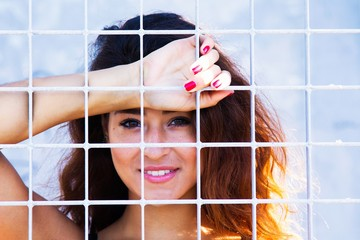 woman leaning behind the lattice