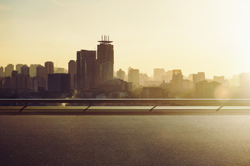 Fotomurales - Empty asphalt road with city skyline background , sunrise or sunset scene .