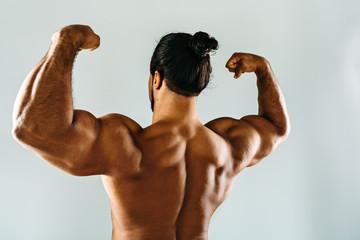 Male bodybuilder posing in studio, showing biceps on hands