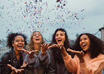 Happy friends standing on a terrace. Group of young women throwing confetti.