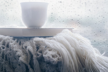 a cup of coffee on a plaid with a book in the background of a window with drops