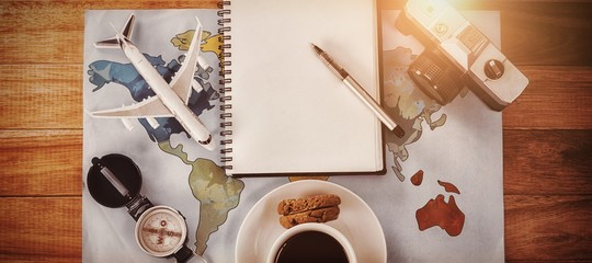 Overhead view of coffee cup with camera and diary map