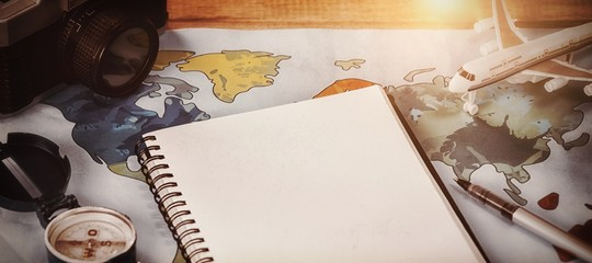 Diary by camera and toy airplane on map