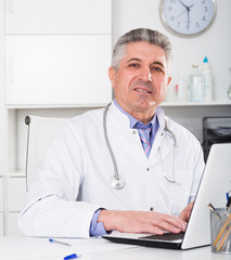 Mature doctor in his office