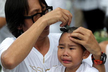 A devotee girl has her hair shaved by her father during a mass novice nun ordination ceremony to mark the first anniversary of late Thailand's King Bhumibol Adulyadej's death, at the Sathira-Dhammasathan Buddhist meditation centre in Bangkok
