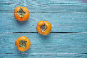 Delicious fresh persimmon on a wooden background. View from above.